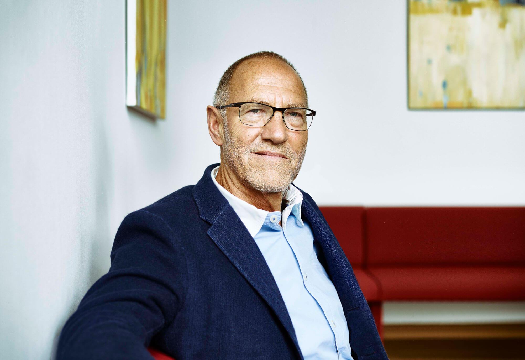 Ralf Dreher von der R-Biopharm AG sitzt auf einem roten Sofa